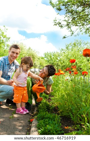 Beautiful family in the garden - stock photo