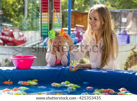 beautiful family mother and daughter playing in the park fishing - stock photo