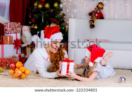 beautiful family mother and her baby on the floor near the Christmas tree on Christmas Eve give gifts to each other - stock photo
