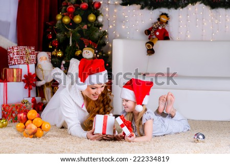 beautiful family mother and her baby on the floor near the Christmas tree on Christmas Eve open box with a gift - stock photo