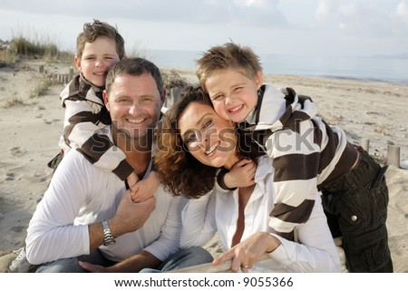 beautiful family of four sitting on the beach