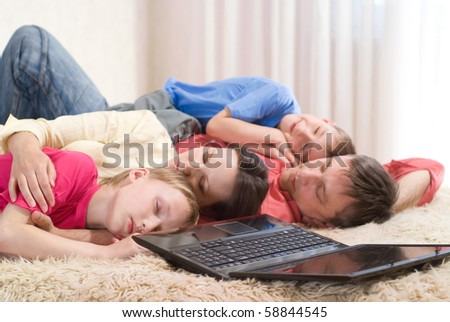 beautiful family of four with a laptop - stock photo