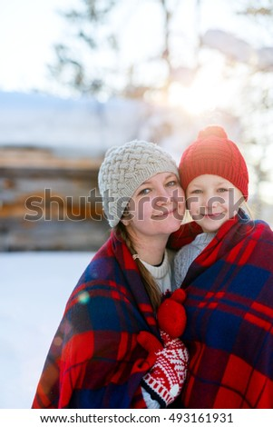 Beautiful family of mother and her little daughter enjoying snowy winter day outdoors