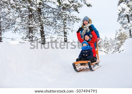 Beautiful family of mother and kids enjoying snowy winter day outdoors having fun sledging