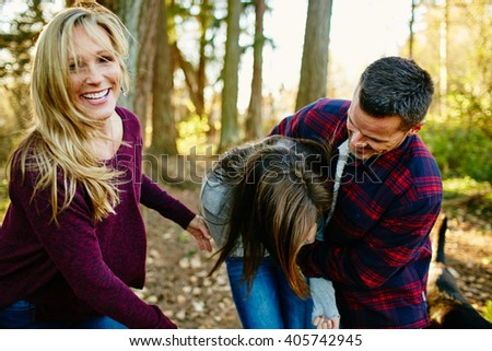 beautiful family of 3 smiling  and laughing walking in forest with sun behind