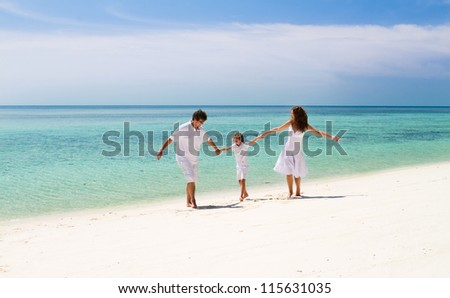 Beautiful family of three dancing on a tropical beach - stock photo