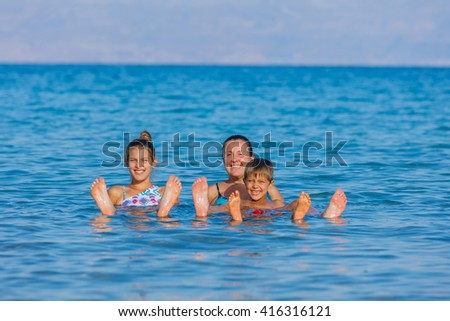 Beautiful family of three floating in the waters of the Dead Sea, Israel