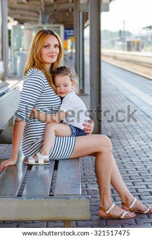 Beautiful family of two: little girl and mother. Hugging and waiting for train on station. People, travel, family, lifestyle concept - stock photo