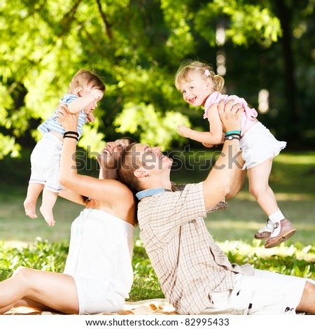 Beautiful family playing in the park - stock photo