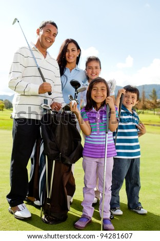 Beautiful family playing together at a golf course - stock photo