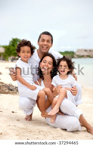 Beautiful family portrait at the beach smiling - stock photo