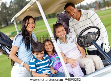 Beautiful family portrait in a cart at the golf course - stock photo