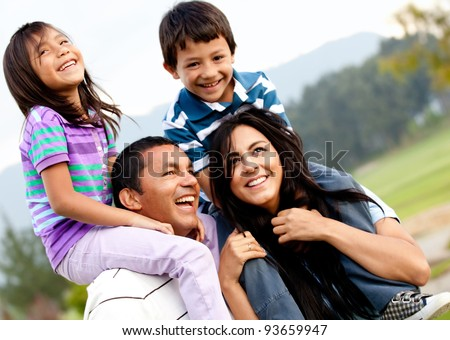 Beautiful family portrait outdoors looking very happy - stock photo