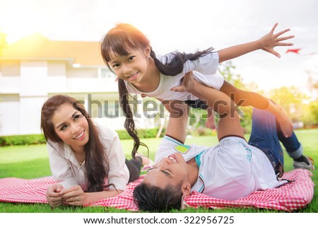 Beautiful family portrait smiling outside their new house, picknic and outdoor concept