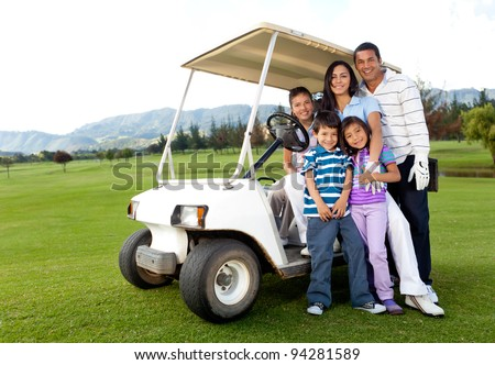 Beautiful family portrait with a cart at the golf course - stock photo