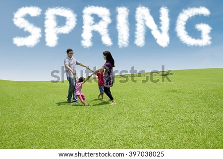Beautiful family smiling happy while playing together and make a circle at field under a spring cloud - stock photo