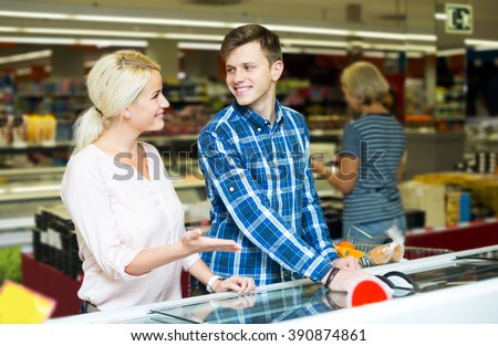 Beautiful family standing near display with frozen food in supermarket. Focus on the man - stock photo