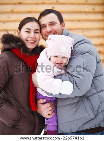 Beautiful family wearing warm clothes standing by wooden house in winter