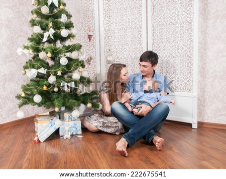 Beautiful family with a baby near Christmas tree. Family Portrait