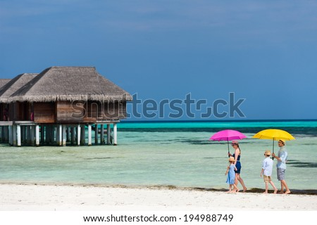 Beautiful family with colorful umbrellas walking along a beach on summer vacation - stock photo
