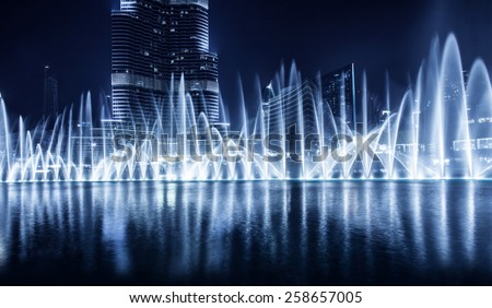 Beautiful famous fountain in Dubai at night, romantic music, water dance, blue lights, luxury resort, evening cityscape - stock photo