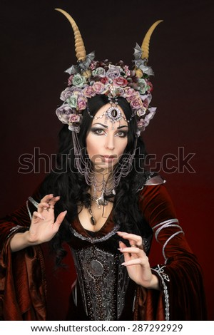 Beautiful fantasy elf woman in flower crown and medieval dress - stock photo