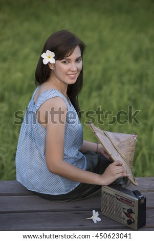 Beautiful Farmer Woman relaxing on the bridge over rice field while listening music by radio.
