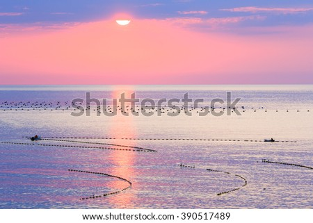 Beautiful fascinate morning sea view with sunrise, sun track on surface and fishing nets. Humans on boat are unrecognizable.