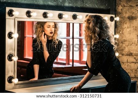 Beautiful fashion blond woman posing near the mirror - stock photo