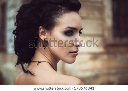Beautiful fashion brunette woman creative hairstyle street portrait. bright make up smoky eyes - stock photo