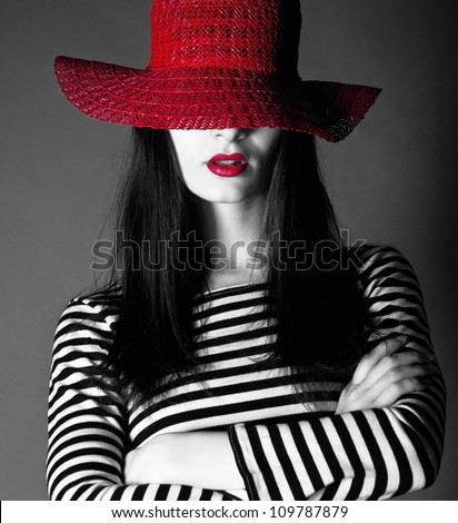 Beautiful fashion brunette woman wearing a red hat and red lipstick in studio environment - stock photo
