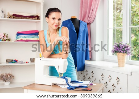 Beautiful fashion designer is working in her workshop. The woman is standing near her sewing mashing and smiling. She is looking forward with enjoyment