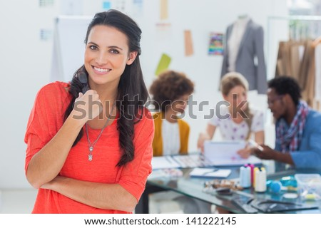 Beautiful fashion designer posing while her team brainstorming behind - stock photo