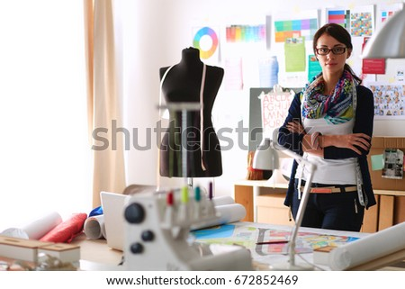 Beautiful fashion designer sitting at the desk in studio .