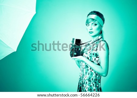 Beautiful fashion girl on the turquoise background with camera