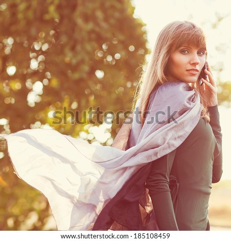 beautiful fashion girl speaks by phone in the park, she develops beautifully scarf - stock photo