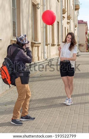 Beautiful fashion girl top model with red balloon posing for a photograph hipster morning on an empty city street - stock photo