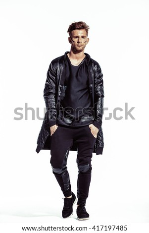 Beautiful fashion male model posing on white background in black clothes. Muscular athletic man. Expression. Brutal man.