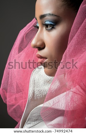 Beautiful fashion model expressing confidence, wearing white leather jacket and wrapped in pink net - stock photo