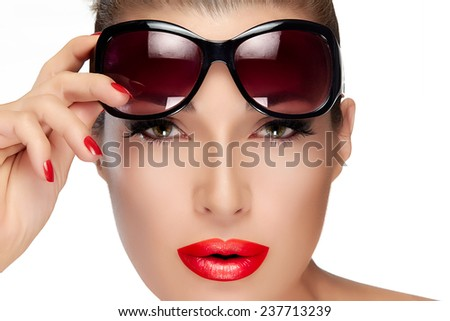 Beautiful fashion model girl holding her shades on Forehead while looking at camera. Isolated on white background. Beauty and fashion concept.