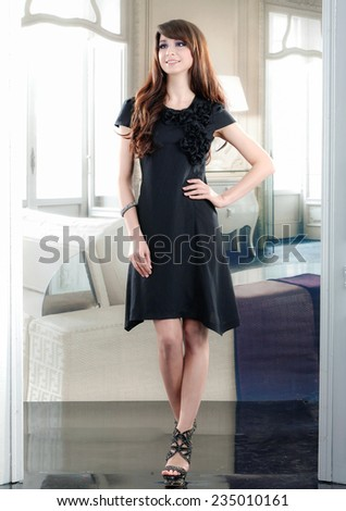 Beautiful fashion model in black dress posing - stock photo