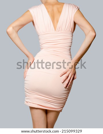 Beautiful fashion model in pink dress from behind isolated on gray background. - stock photo