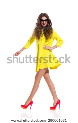 Beautiful fashion model in sunglasses walking in yellow dress and red high heels. Full length studio shot isolated on white. - stock photo