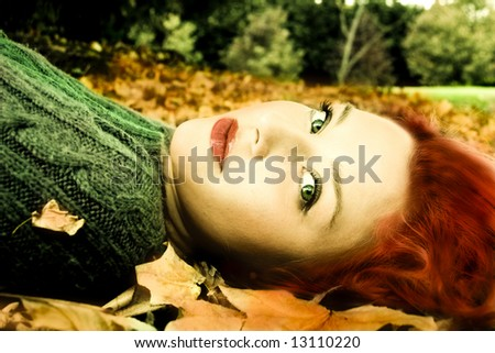 beautiful fashion model lying in the leaves - stock photo