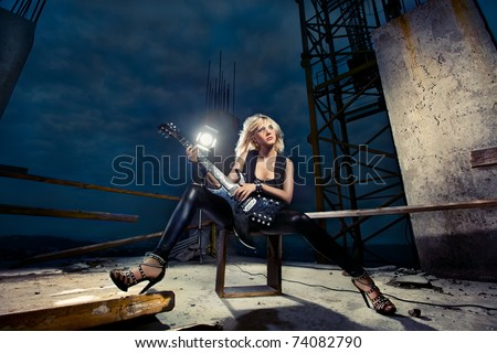 beautiful fashion model playing guitar on a roof top - stock photo