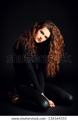 Beautiful fashion model posing at studio. Over black background.