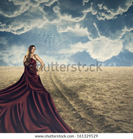 Beautiful fashion model posing with a long silk dress in a surreal beach