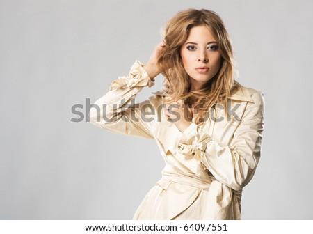 Beautiful fashion model seductively posing in beige coat against gray background - stock photo