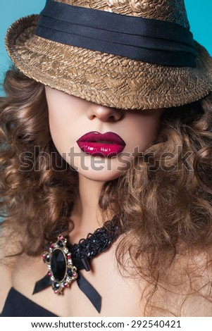 Beautiful fashion model with big red lips and closed eyes with broad-brim (hat) on blue background. looking at camera.  Developed from RAW. retouched with special care and attention.