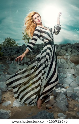 Beautiful fashion model with long hair posing outdoor. - stock photo